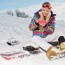 Girl with snowboard sitting on the snow and is making a selfie
